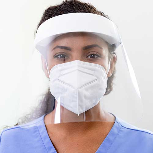 Female medical professional wearing mask and ppe shield