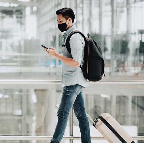 Jeune homme avec valise à roulettes regardant un téléphone portable en marchant à l'aéroport