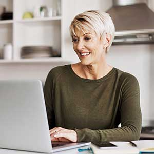 Middle aged woman sitting at table with laptop