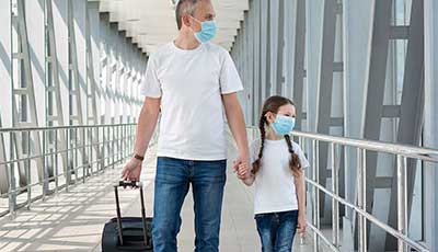 Father and daughter walking through an airport wearing masks
